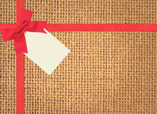 Linen texture background with red ribbon, bow and tag Royalty Free Stock Photo