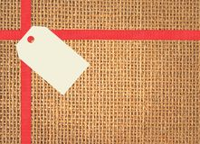 Linen texture with red ribbon and tag Stock Photos
