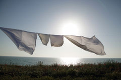 Linens dries in the fresh air. On a background the sea and sunset Stock Photography