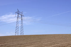Lines. A pillar with power lines stretched across a clear blue sky with a small amount of wispy clouds, with an empty dirt planting field below Stock Image