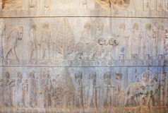 Lines of carved people on the destroyed stone bas-relief in Persepolis Stock Photo