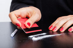 Lines of cocaine. Woman making lines of cocaine with a credit card Royalty Free Stock Photo