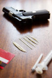 Lines of drug and a pistol on the background Stock Photography