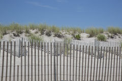 Lines Upon Lines: Beach Fences, Grass, and Sky Stock Photography