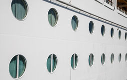 Lines of Portholes on White Bulkhead Royalty Free Stock Photography