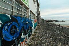 Lines, water and graffiti. Aspect of sidewalk along Tagus river left margin in the city of Lisbon stock photography