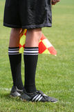 The linesman. Close up of a lines man's legs and flag at a soccer/football game Royalty Free Stock Image