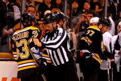 Linesman Bryan Pancich restrains Brad Marchand. Stock Image