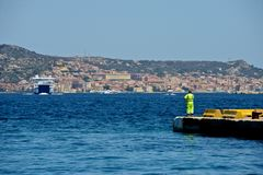 Linesman on a dock and ferry boats navigating in the middle of the sea royalty free stock photo