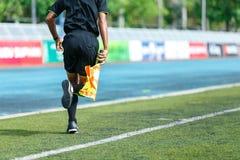 Linesman. Linesman with flag running on football yard Stock Image