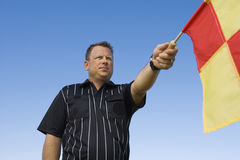 Linesman Showing Penalty Flag Against Blue Sky. Low angle view of linesman showing penalty flag against clear blue sky Royalty Free Stock Images