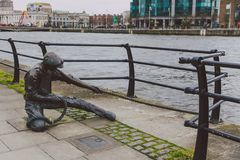 The Linesman statue on the river Liffey on the Dublin`s city qua Stock Photography