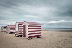 Lineup av röda och vita målade strandkojor arkivfoton