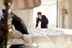 Linge de lit changeant de femme de chambre sur le lit dans une chambre d'hôtel Photos libres de droits