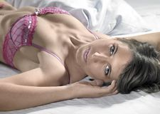 Lingerie dressed lady resting on bed Stock Image