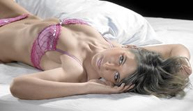 Lingerie dressed lady resting on bed Stock Images