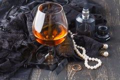 Lingerie et accessoires femelles avec le verre du cognac Photographie stock libre de droits