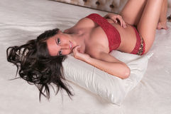 Lingerie Model Lies Back on Pillow Stock Photo
