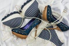 Lingerie, perles et chaussures se trouvant sur la soie blanche Photo stock
