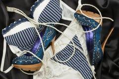 Lingerie, perles et chaussures se trouvant sur la soie noire Image stock