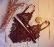 Lingerie roupa interior preto laçado do ` s das mulheres com um busto e cuecas no foco macio do fundo branco de madeira Fotografia de Stock Royalty Free