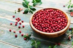 Lingonberry maduro da airela, partridgeberry, foxberry na bacia de madeira no fundo rústico do vintage Imagens de Stock Royalty Free