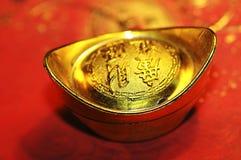 Lingot chanceux chinois d'or sur le backgr rouge de calligraphie Images libres de droits