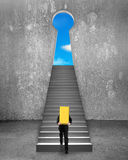 Lingot d'or de transport d'homme d'affaires sur des escaliers pour verrouiller la porte de forme Photographie stock libre de droits