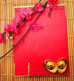 lingot en forme de chaussure d'or (Yuan Bao) et Plum Flowers avec le paquet rouge Photo stock