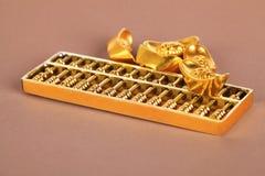 Lingote chinês do ouro e ábaco dourado Fotos de Stock