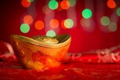 Lingote chino del oro de las decoraciones del Año Nuevo en fondo rojo Imagenes de archivo