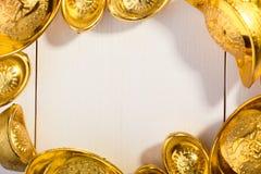 Lingote chino del oro en fondo blanco de madera Foto de archivo