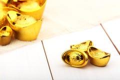 Lingote chino del oro en fondo blanco de madera Imagen de archivo