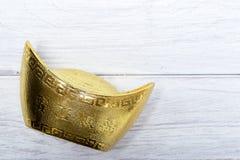 lingote chino del oro en la madera blanca Foto de archivo libre de regalías