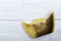 lingote chino del oro en la madera blanca Foto de archivo