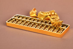 Lingote chino del oro y ábaco de oro Fotos de archivo