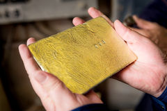 Lingote crudo del oro en las manos Imagen de archivo