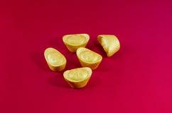 Lingote de oro del oro de la cuña que se casa el fondo rojo Foto de archivo