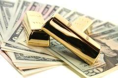 Lingote de ouro em contas de dólar Imagens de Stock Royalty Free