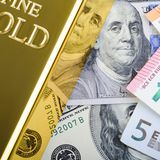 Lingote do lingote da barra de ouro na perspectiva das contas do dólar e do euro imagem de stock