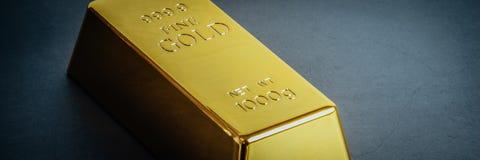 Lingote do lingote da barra de ouro no fundo azul Localizado diagonalmente fotografia de stock