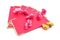 lingote Zapato-formado del oro (Yuan Bao) y Plum Flowers con el paquete rojo Fotos de archivo libres de regalías