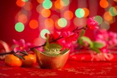 Lingotes chinos del oro de las decoraciones del Año Nuevo en fondo rojo Fotos de archivo