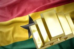 Lingotes de oro brillantes en la bandera de Ghana Fotografía de archivo libre de regalías