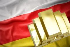 Lingotes de oro brillantes en la bandera de Osetia del Sur Imagenes de archivo