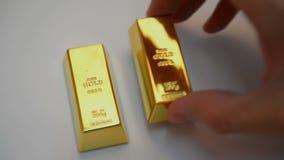 Lingotes del oro en el fondo blanco almacen de video
