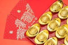 Lingotes del oro en el sobre rojo de China en el Año Nuevo chino Foto de archivo