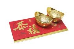 Lingotes del oro y paquete rojo Fotos de archivo