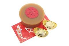 Lingotes do ouro; Pacote vermelho e bolo chinês do ano novo Imagens de Stock