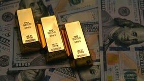 Lingotes e dólares do ouro em uma tabela com obscuridade ao efeito brilhante